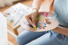 Artista che si applica pittura alla tavolozza allo studio di arte Fotografie Stock
