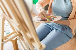 Artista che si applica pittura alla tavolozza allo studio di arte Immagini Stock