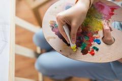 Artista che si applica pittura alla tavolozza allo studio di arte Immagini Stock Libere da Diritti