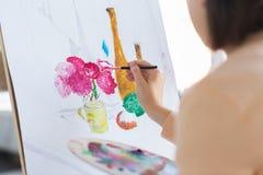 Artista com a escova que pinta ainda a vida no estúdio Foto de Stock Royalty Free