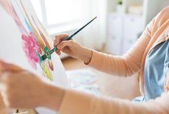 Artista com a escova que pinta ainda a vida no estúdio Fotos de Stock