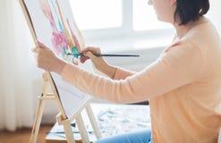 Artista com a escova que pinta ainda a vida no estúdio Fotos de Stock Royalty Free