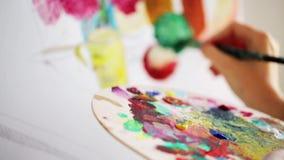 Artista com pintura da paleta e da escova no estúdio filme