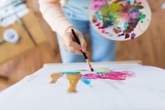 Artista com pintura da paleta e da escova no estúdio Fotos de Stock Royalty Free