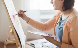 Artista com pintura da paleta e da escova no estúdio Fotografia de Stock