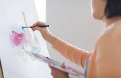 Artista com pintura da paleta e da escova no estúdio Imagens de Stock