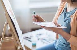 Artista com pintura da paleta e da escova no estúdio Foto de Stock Royalty Free