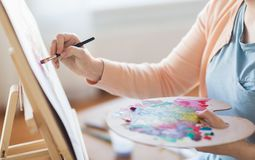 Artista com pintura da paleta e da escova no estúdio Foto de Stock