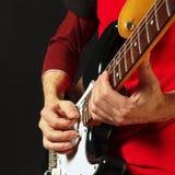 Artista con la guitarra eléctrica en fondo negro Imagenes de archivo