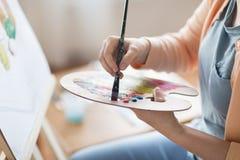 Artista con la pittura della tavolozza allo studio di arte Immagini Stock Libere da Diritti