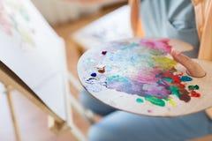 Artista con la pittura della tavolozza della pittura allo studio di arte Immagine Stock