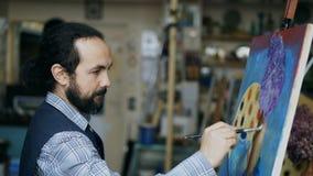 Artista concentrado do homem que pinta ainda a imagem da vida na lona no estúdio da arte dentro Foto de Stock
