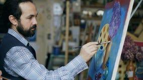 Artista concentrado do homem que pinta ainda a imagem da vida na lona no estúdio da arte dentro Fotografia de Stock