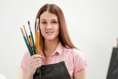 Artista da jovem mulher com escovas e pinturas em um estúdio branco imagens de stock royalty free