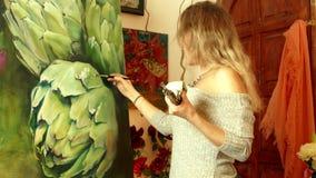 Artista da jovem mulher que pinta uma grande alcachofra realística filme