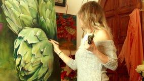 Artista da jovem mulher que trabalha em um estúdio que pinta uma alcachofra vídeos de arquivo