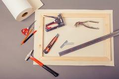 Artista da lona no rolo, maca para a lona, arma do grampo e outras ferramentas em um fundo cinzento Imagens de Stock Royalty Free