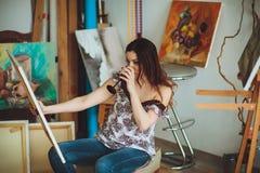 Artista da mulher que pinta uma imagem em um estúdio Imagens de Stock
