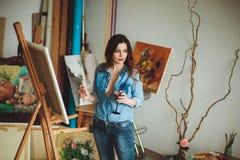 Artista da mulher que pinta uma imagem em um estúdio Foto de Stock Royalty Free