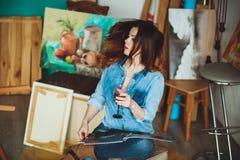 Artista da mulher que pinta uma imagem no estúdio do sótão Foto de Stock Royalty Free