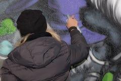 Artista da rua da moça: Pulverização na parede urbana pública da cidade Foto de Stock