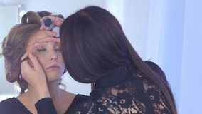 Artista de composição profissional que aplica o lápis de olho em torno do olho inteiro do modelo Imagens de Stock