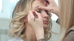 Artista de composição profissional que aplica o lápis de olho na pálpebra Fotos de Stock Royalty Free