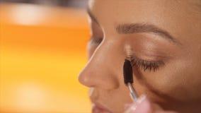 Artista de composição que aplica a composição da pestana ao olho modelo do ` s Feche acima da vista vídeos de arquivo