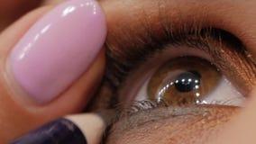 Artista de composição que aplica o lápis de olho filme