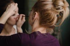 Artista de composição que aplica a sombra brilhante da cor baixa no olho do modelo Fotografia de Stock Royalty Free