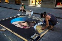 Artista de la calle que dibuja a la muchacha con un pendiente de la perla en el asfalto Imagen de archivo