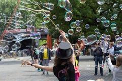 Artista de la calle que hace burbujas de jabón en la calle Foto de archivo libre de regalías