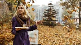 Artista de la chica joven que presenta entre las hojas que caen con el caballete en parque del otoño fotos de archivo libres de regalías