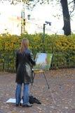 Artista de la muchacha que pinta un paisaje del otoño fotos de archivo