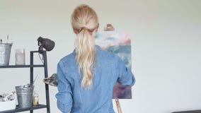 Artista de la mujer joven que pinta en casa la visión trasera de pintura creativa almacen de metraje de vídeo