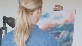 Artista de la mujer joven que pinta en casa la visión trasera de pintura creativa almacen de video