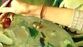 Artista de la mujer joven que pinta una imagen de las ilustraciones usando la paleta de la pintura al óleo almacen de metraje de vídeo