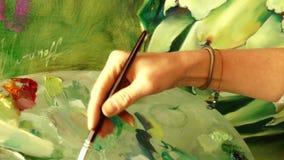 Artista de la mujer joven que pinta una imagen de las ilustraciones usando la paleta de la pintura al óleo almacen de video