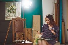 Artista de la mujer que pinta una imagen en estudio del desván Imágenes de archivo libres de regalías