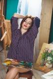 Artista de la mujer que pinta una imagen en estudio del desván Imagen de archivo libre de regalías