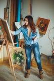 Artista de la mujer que pinta una imagen en un estudio Imagen de archivo libre de regalías