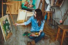 Artista de la mujer que pinta una imagen en un estudio Imágenes de archivo libres de regalías