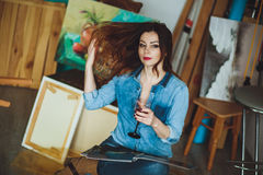 Artista de la mujer que pinta una imagen en un estudio Imagenes de archivo