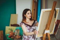 Artista de la mujer que pinta una imagen en un estudio Fotos de archivo libres de regalías