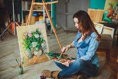 Artista de la mujer que pinta una imagen en un estudio Fotografía de archivo libre de regalías