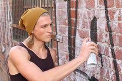 Artista de la pintada que rocía en la pared de ladrillo Fotos de archivo