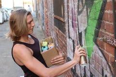 Artista de la pintada que rocía en la pared de ladrillo Imágenes de archivo libres de regalías
