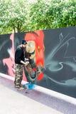 Artista de la pintada que rocía la pared Imagen de archivo libre de regalías