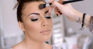 Artista de maquillaje Applying Lipstick a la mujer bonita Fotos de archivo