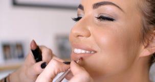 Artista de maquillaje Applying Lipstick a la mujer bonita Imágenes de archivo libres de regalías